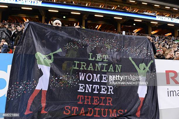 Supporters hold a banner reading 'Let Iranian women enter their stadiums' during the friendly international football match between Sweden and Iran at...