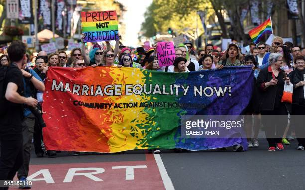 Supporters hold a banner while marching as they attend a samesex marriage rally in Sydney on September 10 2017 Thousands of samesex marriage...