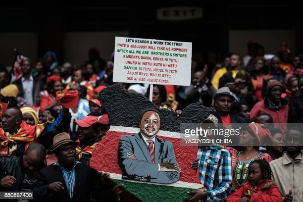 Supporters hold a placard reading 'Let's reason and work together' during the inauguration ceremony of Kenya's President Uhuru Kenyatta at Kasarani...
