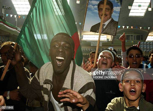 Supporters hold a poster of Ali Benflis , secretary general of the ruling National Liberation Front and presidential candidate, during a meeting 01...