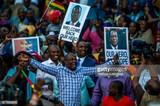 Supporters hold banner wave Zimbabwean national flag and cheer as they gather to welcome Zimbabwe's incoming President Emmerson Mnangagwa upon his...