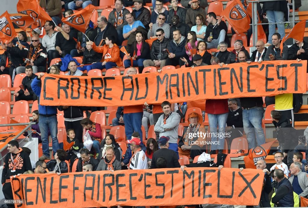 Supporters hold banners during the French L1 football match Lorient vs Caen at the Moustoir stadium in Lorient, western France, on April 2, 2017. 'Believing in retaining (the French Ligue 1) is good, doing it is better' /