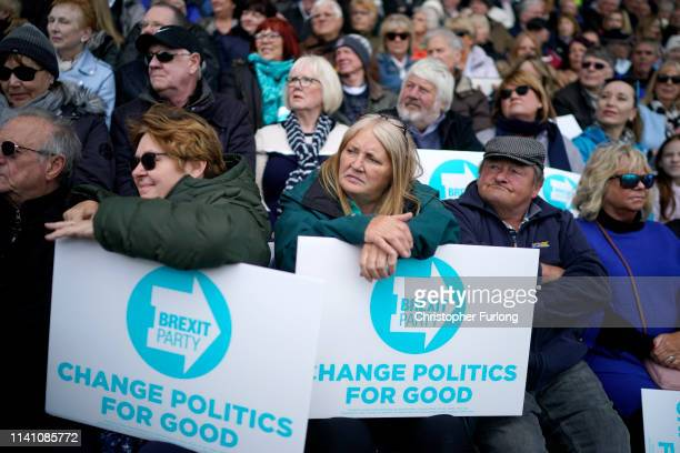 Supporters hold Brexit Party signs during a Brexit Party campaign rally at Mill Farm home of AFC Flyde on May 4 2019 in Wesham United Kingdom Nigel...