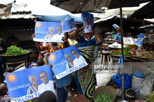 Supporters hold campaign posters with photographs of incumbent Benin President Patrice Talon and running mate Mariam Talata in the market in Cotonou...