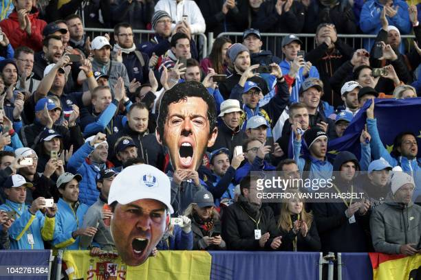 Supporters hold cardboard cutouts depicting Europe's Northern Irish golfer Rory McIlroy and Europe's Spanish golfer Sergio Garcia during the fourball...
