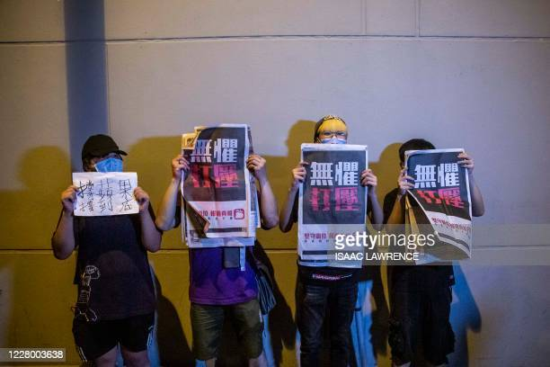 Supporters hold copies of the Apple Daily newspaper as Hong Kong pro-democracy media mogul Jimmy Lai is released on bail from the Mong Kok police...