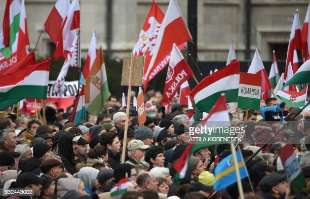 Supporters hold Hungarian and Polish flags as the Hungarian Prime Minister delivers a speech in Budapest on March 15 during the official...