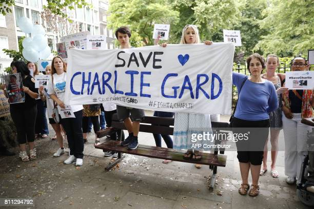 Supporters hold placards as they wait for Connie Yates and Chris Gard parents of terminallyill 10monthold Charlie Gard prior to his parents...