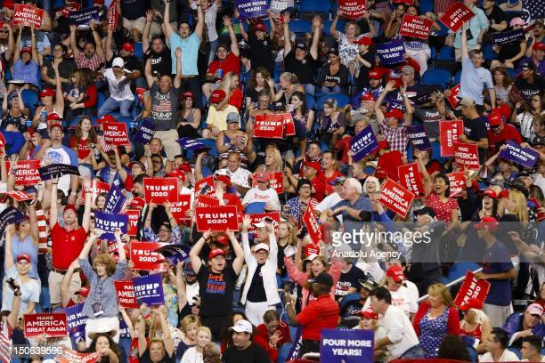 Supporters hold placards during a rally at the Amway Center in Orlando, Florida, United States on June 18, 2019. President Donald Trump officially...