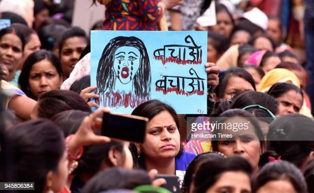Supporters hold placards during the hunger strike by Swati Maliwal Delhi Commission for Women chief against Unnao and Kathua rape cases near Rajghat...
