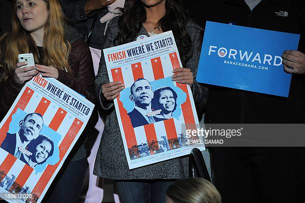 Supporters hold poster as US President Barack Obama speaks at his last campaign rally in Des Moines Iowa on November 5 2012 After a grueling 18month...