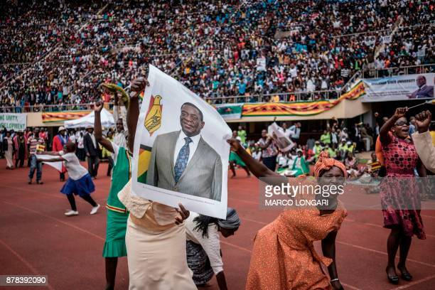 TOPSHOT Supporters hold poster of the newly swornin President Emmerson Mnangagwa during the Inauguration ceremony at the National Sport Stadium in...