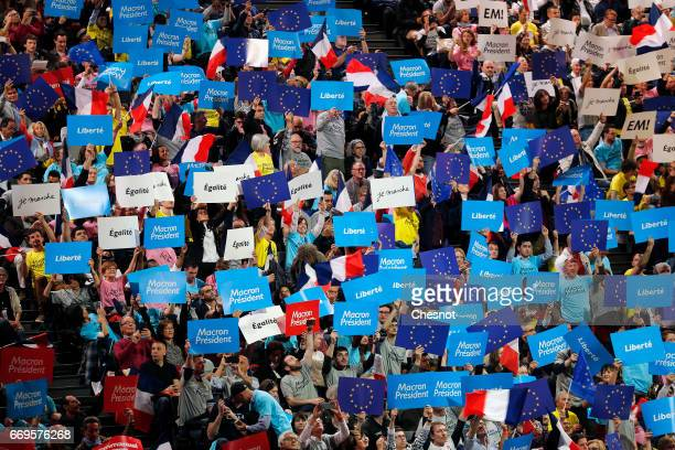 Supporters hold posters French and European flags during a campaign political rally of French presidential election candidate from the centrist 'En...