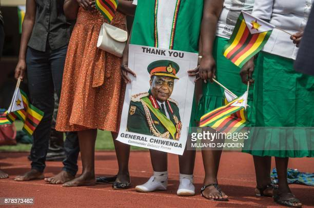 TOPSHOT Supporters hold posters of Zimbabwe Army Chief of Staff General Constantino Chiwenga during newly swornin President Inauguration ceremony at...