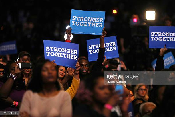 Supporters hold signs as Democratic presidential nominee former Secretary of State Hillary Clinton speaks during a Get Out The Vote concert at...