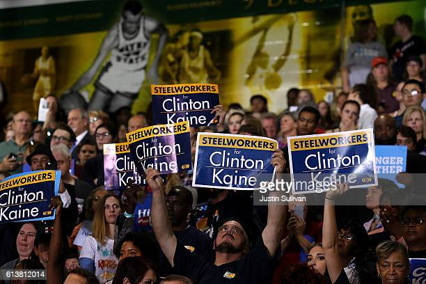 Supporters hold signs as emocratic presidential nominee former Secretary of State Hillary Clinton speaks during a campaign rally at Wayne State...
