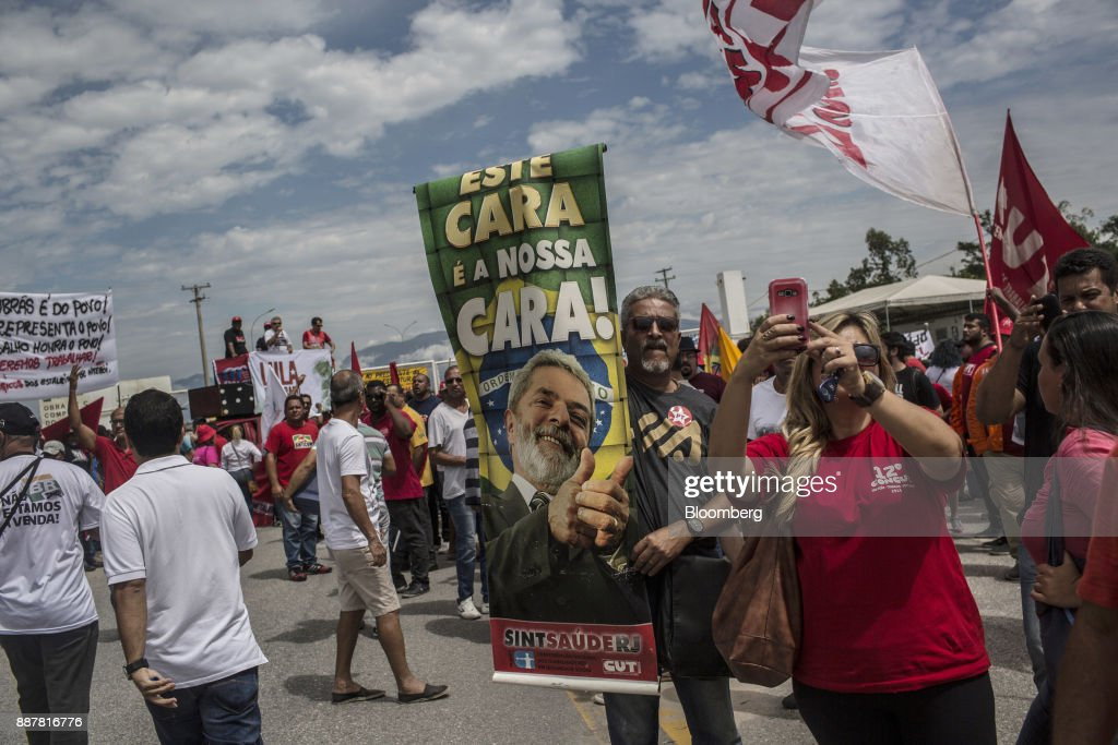 Supporters hold signs during a presidential pre-campaign rally with Brazil's Former President Luiz Inacio Lula da Silva outside the Petroleo Brasileiro SA (Petrobras) Petrochemical Complex in Itaborai, Brazil, on Thursday, Dec. 7, 2017. Brazil's 2018 presidential race is shaping up to be an inflection point in the nation's three-decade-old democracy. While markets are hoping for a centrist, reformist candidate, polls show Lula leading despite a conviction on corruption charges that may bar him from running. Photographer: Dado Galdieri/Bloomberg via Getty Images