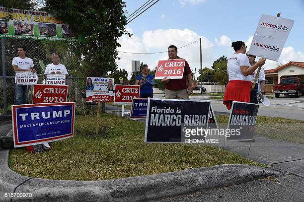 Supporters hold signs for Republican candidates in front of polling precinct for the Florida Primary on March 15 2016 in Miami Florida Voters began...