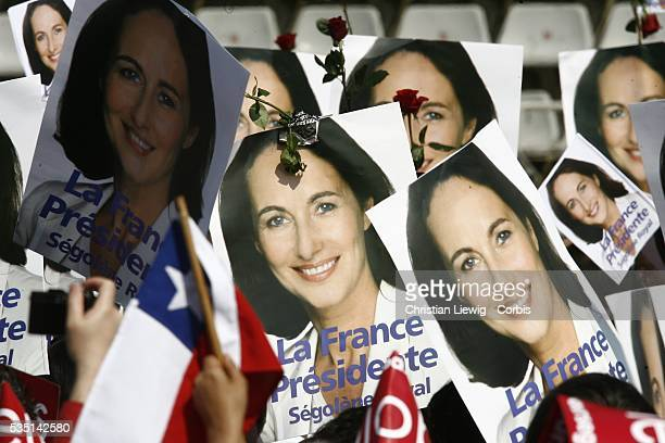 Supporters hold signs of Socialist presidential candidate Segolene Royal and roses symbol of the French Socialist party at a campaign rally for Royal...
