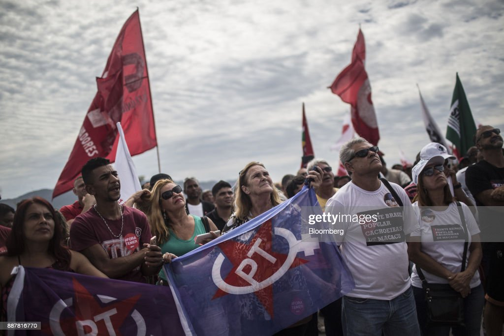 Supporters hold signs while Luiz Inacio Lula da Silva, former president of Brazil, not pictured, speaks during a presidential pre-campaign rally outside the Petroleo Brasileiro SA (Petrobras) Petrochemical Complex in Itaborai, Brazil, on Thursday, Dec. 7, 2017. Brazil's 2018 presidential race is shaping up to be an inflection point in the nation's three-decade-old democracy. While markets are hoping for a centrist, reformist candidate, polls show Lula leading despite a conviction on corruption charges that may bar him from running. Photographer: Dado Galdieri/Bloomberg via Getty Images
