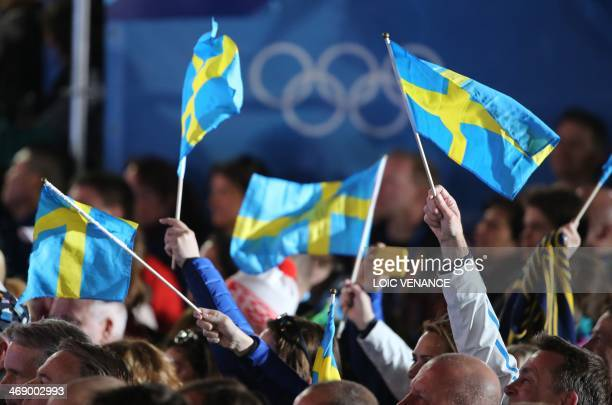 Supporters hold Swedish flags during a Medal Ceremony at the Sochi medals plaza during the Sochi Winter Olympics on February 12 2014 AFP PHOTO / LOIC...