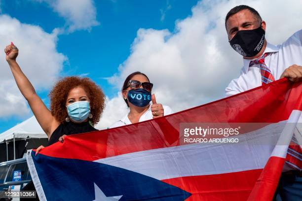 Supporters hold the Puerto Rican flag as former US President Barack Obama speaks at a Biden-Harris drive-in rally in Orlando, Florida on October 27,...