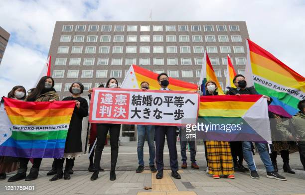 """Supporters hold the """"unconstitutional decision"""" flag as they are pleased with the Sapporo District Court's decision that it is unconstitutional to..."""