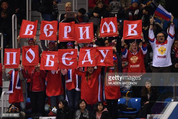 """Supporters hold up cyrilic letters that read """"believe in victory"""" as Russia's Alina Zagitova competes in the women's single skating free skating of..."""