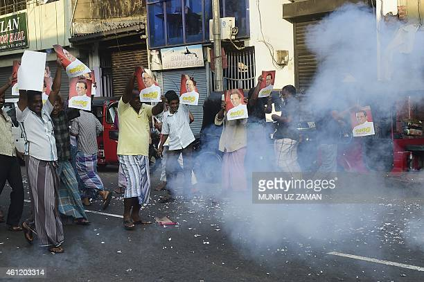 Supporters hold up images of Sri Lanka's Maithripala Sirisena and set off firecrackers as they celebrate in the streets of Colombo after Sri Lanka's...