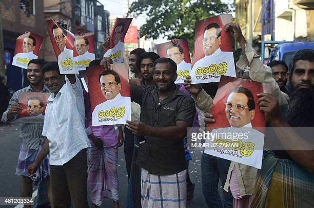 Supporters hold up images of Sri Lanka's Maithripala Sirisena as they celebrate in the streets of Colombo after Sri Lanka's President Mahinda...