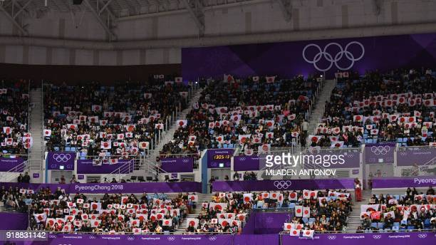TOPSHOT Supporters hold up Japanese flags in the stands during the men's single skating short program of the figure skating event where compatriots...
