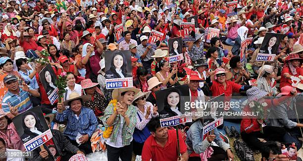 Supporters hold up pictures of candidate for the opposition Puea Thai party Yingluck Shinawatra the sister of former prime minister Thaksin...