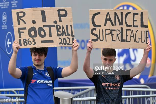 Supporters hold up placards critical of the idea of a New European Super League, outside English Premier League club Chelsea's Stamford Bridge...
