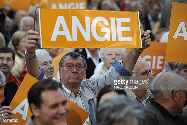 Supporters hold up placards reading 'Angie' as German Chancellor Angela Merkel delivers a speech during an electoral meeting in Hannover northern...
