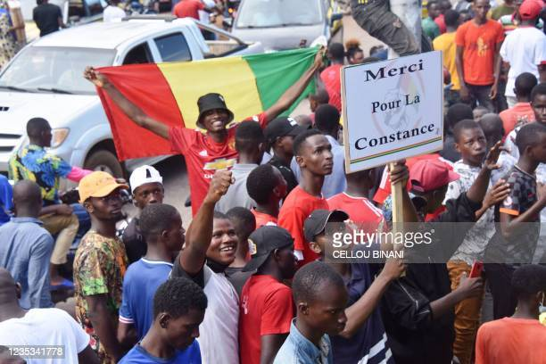 Supporters hold up sign as exiled activists arrive in Conakry, on September 18, 2021. - Guinea's ruling junta on September 18, 2021 ruled out exile...