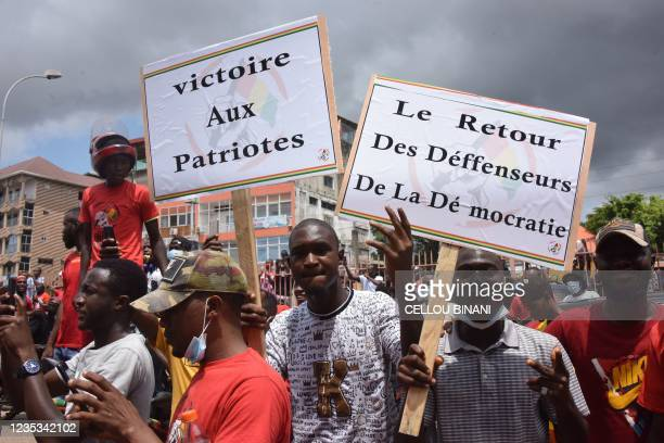 Supporters hold up sign reading victory to the patriots and the return of the defenders of democracy, ahead of the arrival of exiled activists in...