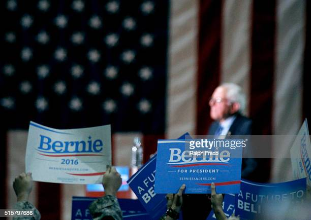 Supporters hold up signs as Democratic presidential candidate Sen Bernie Sanders speaks at the Phoenix Convention Center during a campaign rally on...