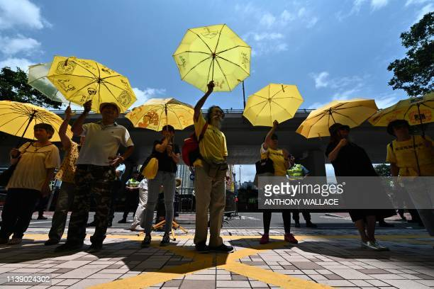 TOPSHOT Supporters hold yellow umbrellas after four prodemocracy activists were sentenced at the West Kowloon Magistrates Court in Hong Kong on April...