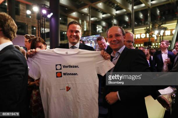 Supporters holding a tshirt celebrate at a Liberal Party rally in The Hague Netherlands on Wednesday March 15 2017 Dutch Prime Minister Mark Ruttes...