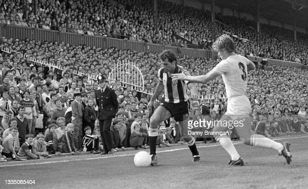 Supporters in the West Stand and a policeman on duty watch the action as Newcastle United striker Imre Varadi takes on Chelsea full back Chris...