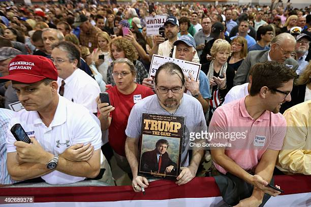 Supporters including a man with a Trump board game wait for presidential candidate and Republican frontrunner Donald Trump at a campaign rally at the...