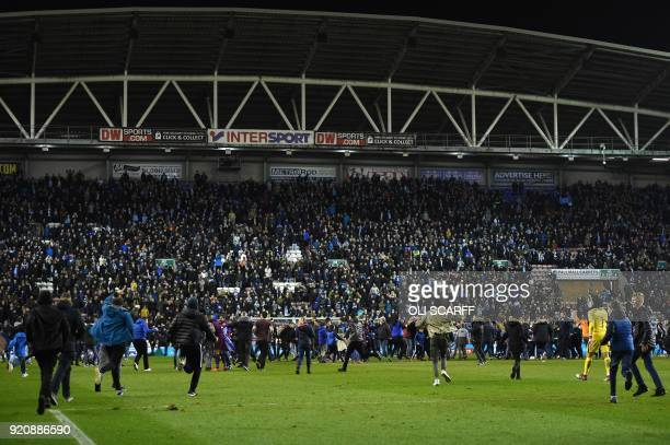 Supporters invade the pitch after the English FA Cup fifth round football match between Wigan Athletic and Manchester City at the DW Stadium in Wigan...