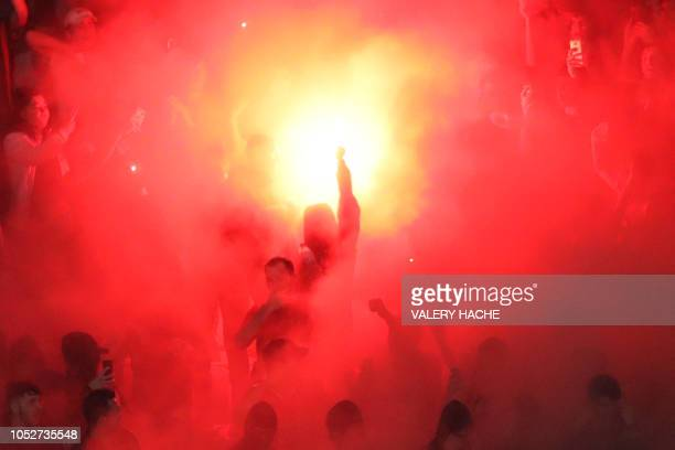 Supporters light flares and wave banners during the French L1 football match between Nice and Marseille at the Allianz Riviera stadium in Nice...