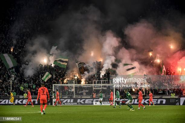 TOPSHOT Supporters light flares and wave flags during the French L1 football match between AS SaintEtienne and Paris SaintGermain at the Geoffroy...