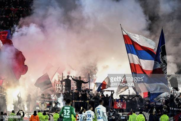 TOPSHOT Supporters light flares and wave flags during the French L1 football match between Olympique Lyonnais and AS SaintEtienne on March 1 2020 at...