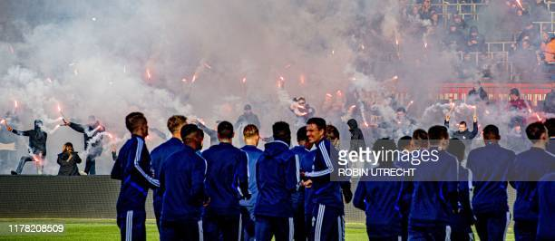 Supporters light flares as they encourage the players of Feyenoord during a training in the run-up to the match against Ajax Amsterdam, in Rotterdam,...