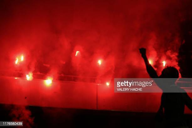 Supporters light flares during the French L1 football match between OGC Nice and Paris SaintGermain at Allianz Riviera stadium in Nice southern...