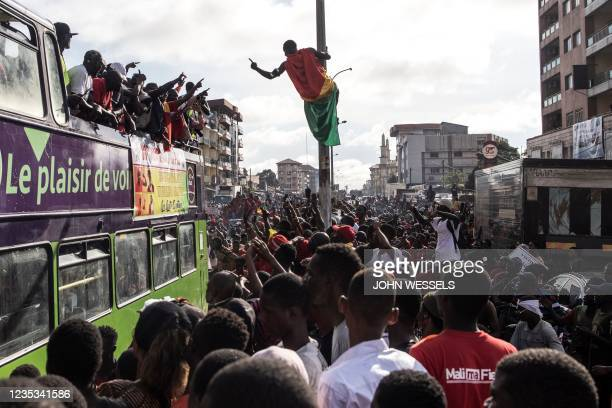 Supporters line the streets as exiled activists ride on a bus after arriving in Conakry, on September 18, 2021. - Guinea's ruling junta on September...