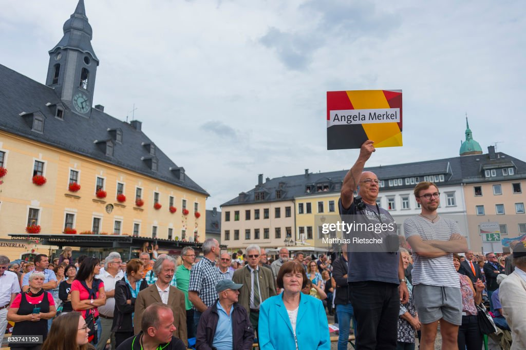 Supporters listen as German Chancellor and head of the German Christian Democrats (CDU) Angela Merkel delievers a speech during an election rally in the state of Saxony on August 17, 2017 in Annaberg-Buchholtz, Germany. Germany is scheduled to hold federal elections on September 24 and Merkel, who is running for a fourth term as chancellor, currently holds a double-digit lead over Martin Schulz from the German Social Democrats (SPD), her main opponent.