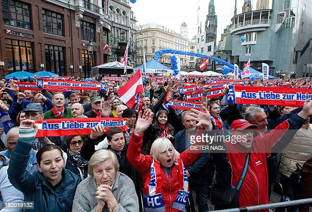 Supporters listen to Austrian Freedom party head and main candidate HeinzChristian Strache speaking during a rally on September 27 2013 ahead of next...